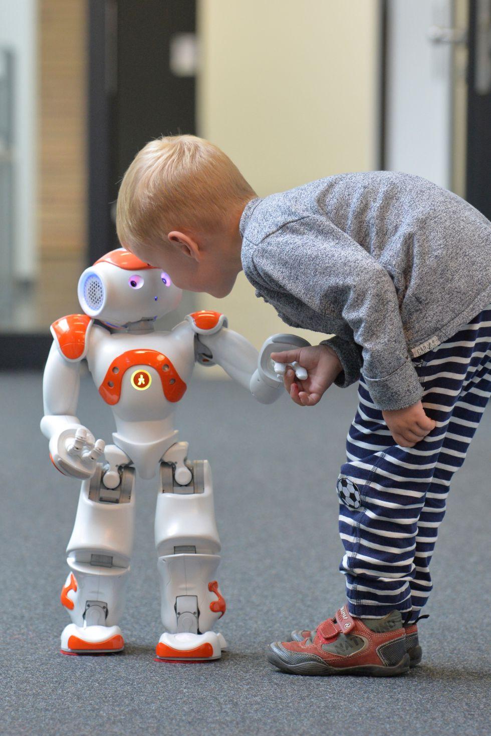 Un niño intenta comunicarse con el robot Neo.