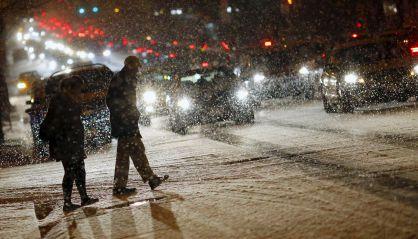 Peatones cruzando una calle en la que empieza a cuajar la nieve.