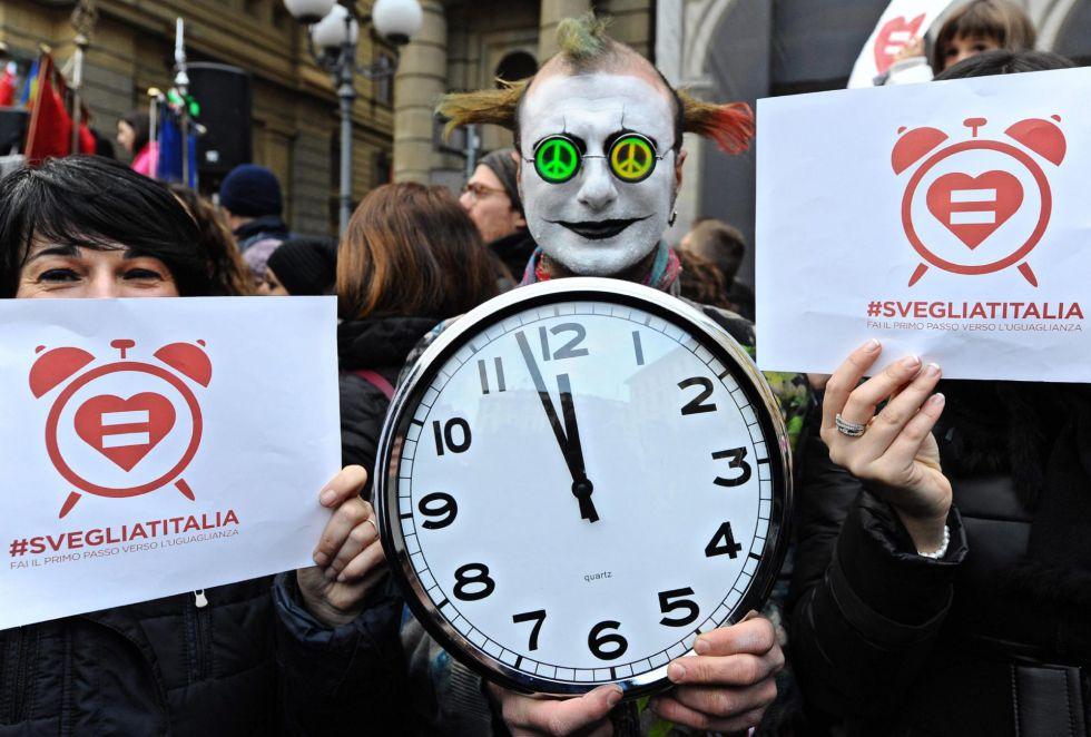 Manifestantes por el reconocimiento de las uniones gais en Florencia con carteles con el lema 'Despierta Italia'.