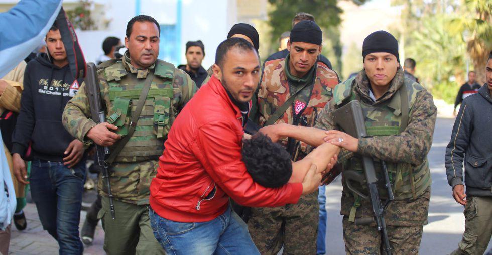 Un ciudadanos y vario soldados llevan a un joven que trató de quemarse a  lo bonzo en una protesta el viernes en Kaserín.