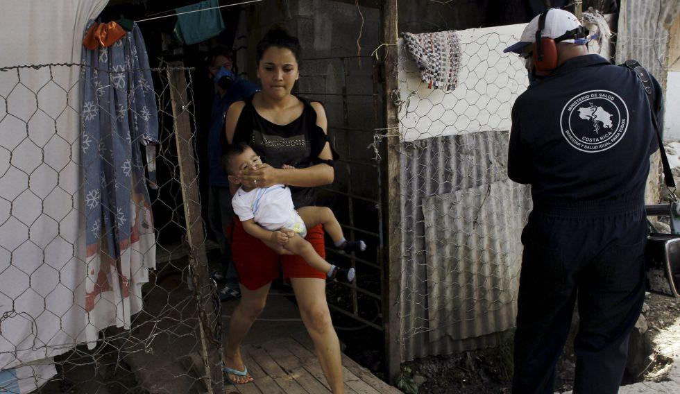 Una mujer cubre la boca de su bebé mientras un operario fumigaba ayer su chabola en el suburbio de El Capio, en San José de Costa Rica.