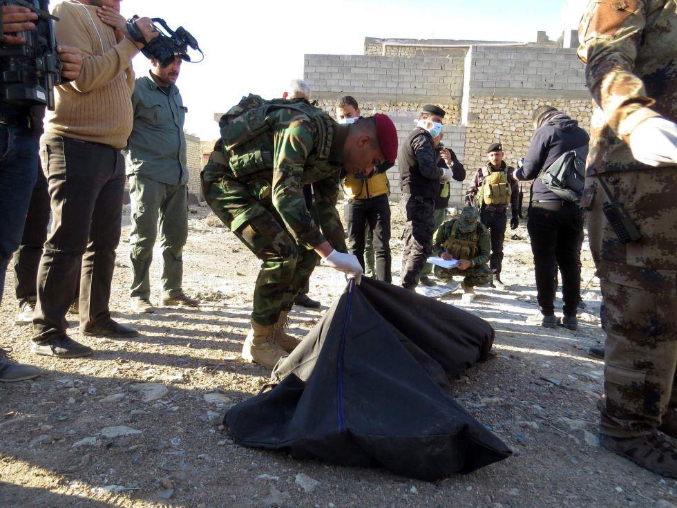 Un soldado con restos de asesinados por el ISIS