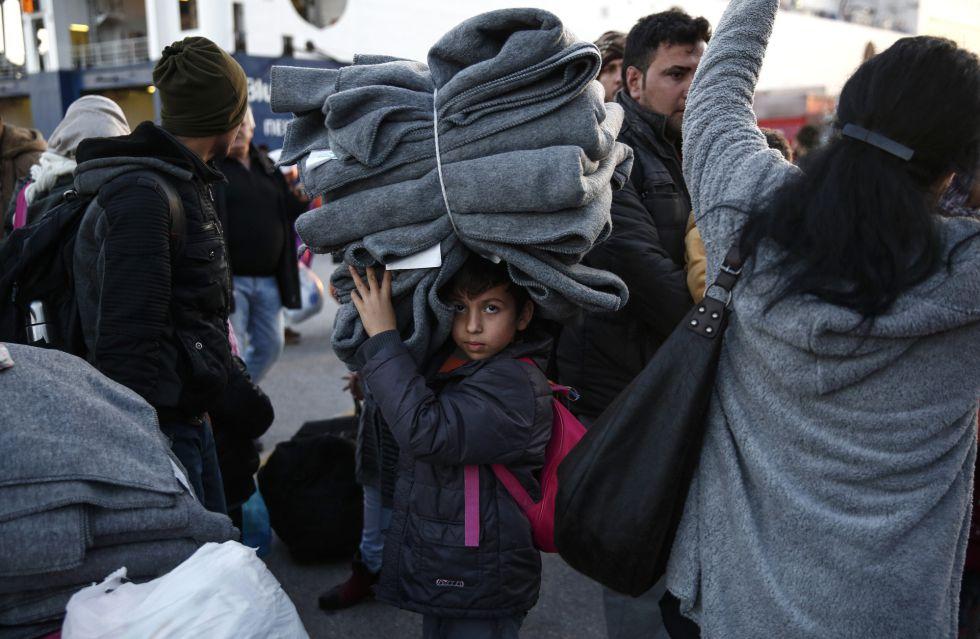 Un niño traslada mantas tras su llegada con otros cientos de refugiados al puerto del Pireo.