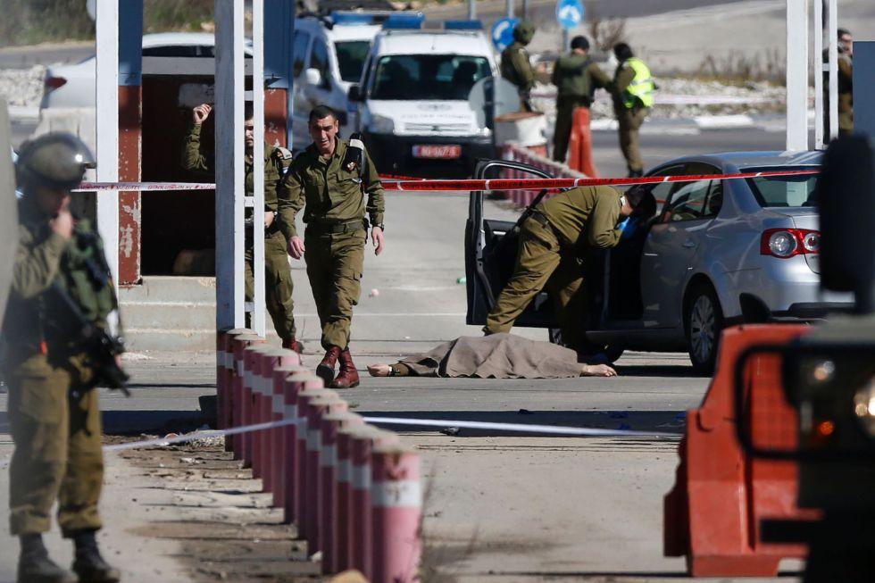 Soldados israelíes junto al cuerpo de un palestino que disparó el pasado domingo en el paso militar Beit El, cerca de Ramala.