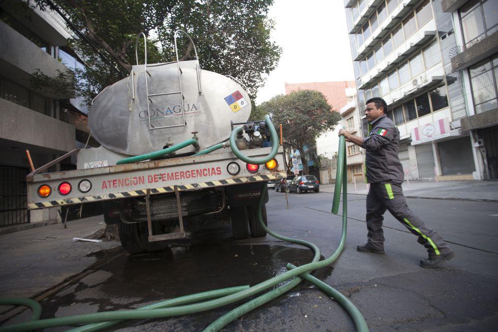 El operador de una pipa llena la cisterna de un edificio a petición de los vecinos.