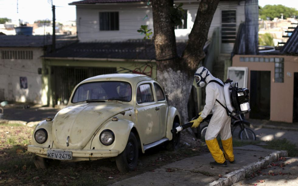Un trabajador fumiga un coche, ayer en Brasil.