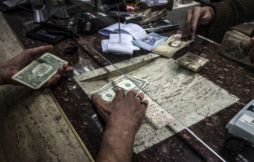 Un comprador recibe dólares en una casa de cambio en Caracas.