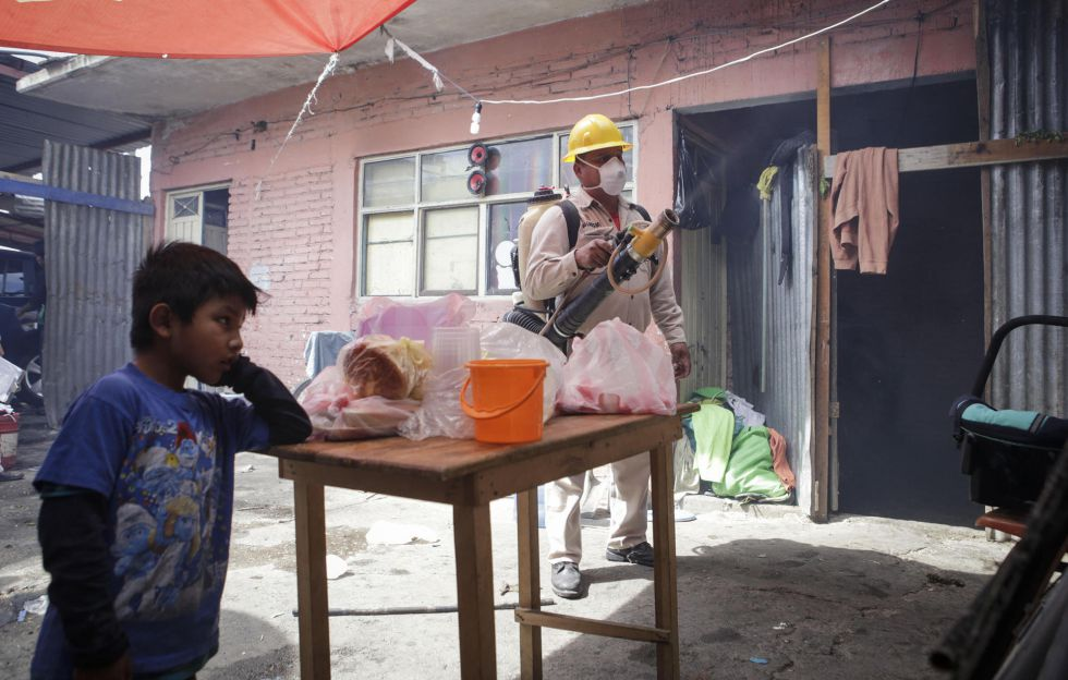 Un empleado de sanidad fumiga una vivienda en Oaxaca, México.