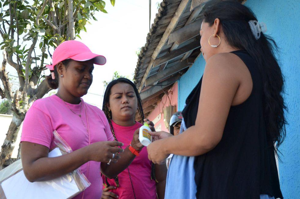 Una trabajadora proporciona repelente y preservativos a varias mujeres en Barranquilla, Colombia, en la campaña contra el zika.