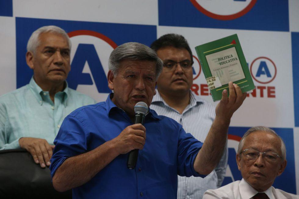 El candidato César Acuña sostiene el libro que plagió