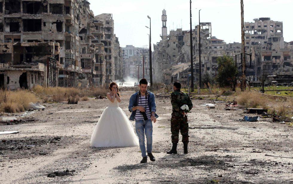 VIDA MÁS ALLÁ DE LA GUERRA. Dos recién casados sirios, Nada Merhi, de 18 años, y el soldado del régimen Hassan Youssef, de 27, posan el viernes para sus fotos de boda en mitad de la destrucción de Homs. El fotógrafo dice que quiere reflejar que la vida es más fuerte que la muerte.