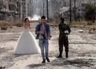 <B>VIDA MÁS ALLÁ DE LA GUERRA.<B> Dos recién casados sirios, Nada Merhi, de 18 años, y el soldado del régimen Hassan Youssef, de 27, posan el viernes para sus fotos de boda en mitad de la destrucción de Homs. El fotógrafo asegura que quiere reflejar que la vida es más fuerte que la muerte.