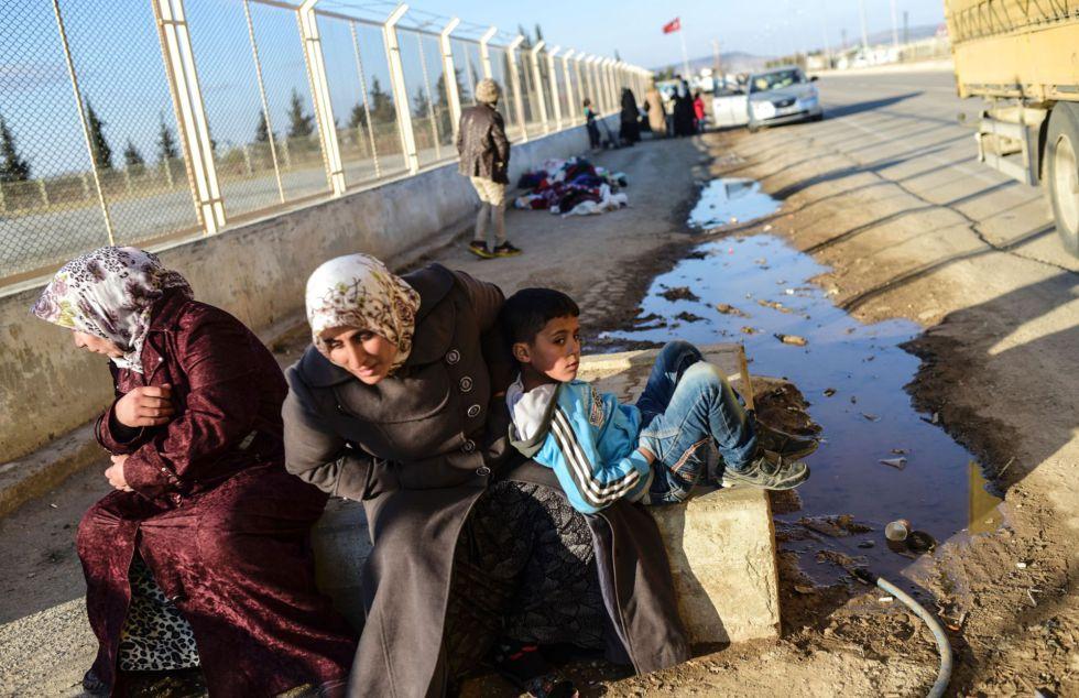 Dos refugiadas sirias y un niño esperan cruzar el paso fronterizo turco de Öncüpinar, cerca de Kilis, para volver a su país.
