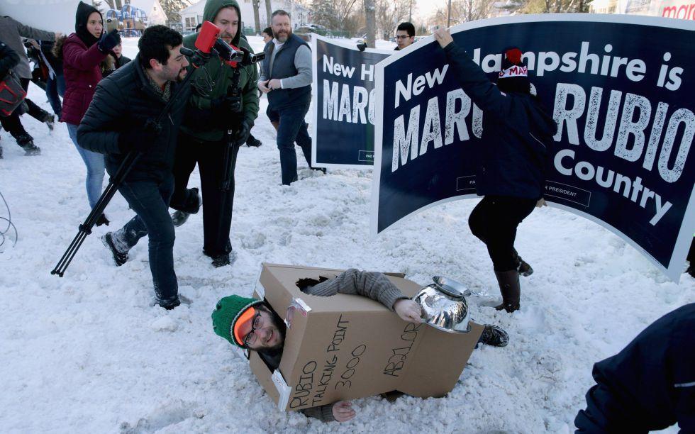 Un manifestante disfrazado de robot cae al suelo ante seguidores de Rubio.