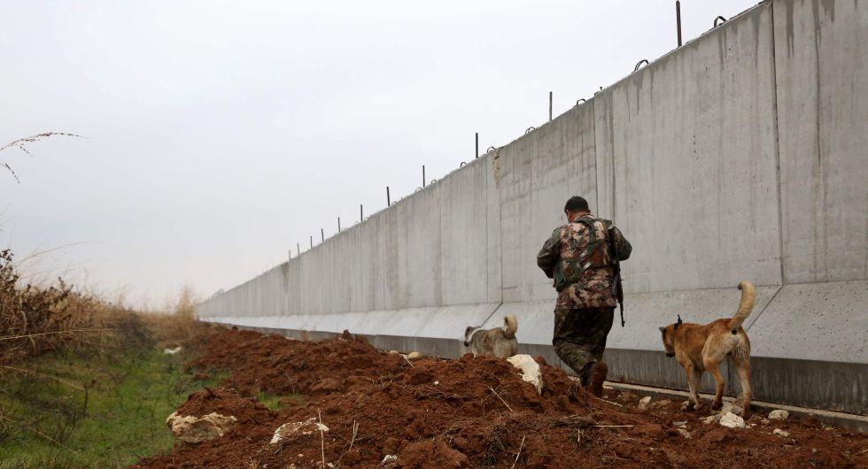 Un combatiente kurdo camina la semana pasada cerca del muro de la frontera turco-siria.