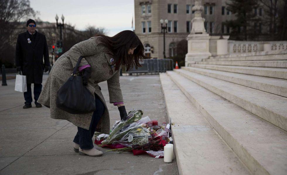 Una mujer deposita flores en homenaje a Scalia en el Supremo