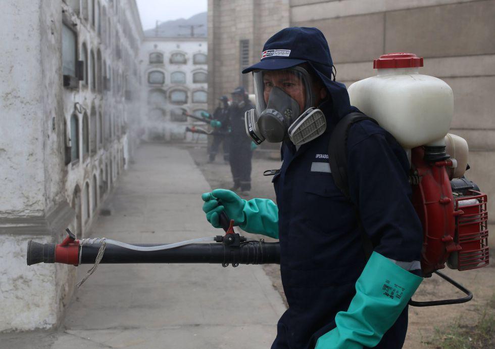 Un trabajador fumiga un cementerio en Lima (Peru), para luchar contra el mosquito Aedes, el 12 de febrero.