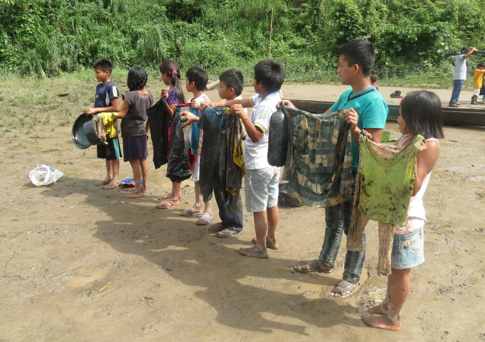 Niños que recogieron petróleo muestran sus camisetas.