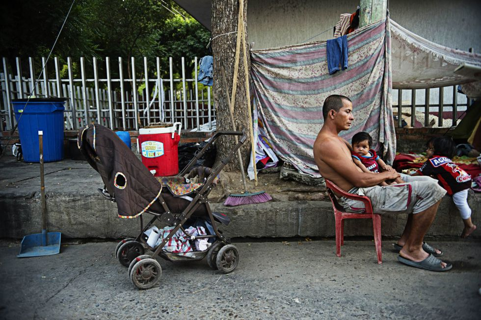 Jhon Jairo Beltrán con el menor de sus hijos en el campamento improvisado donde vive en Cúcuta, Colombia.