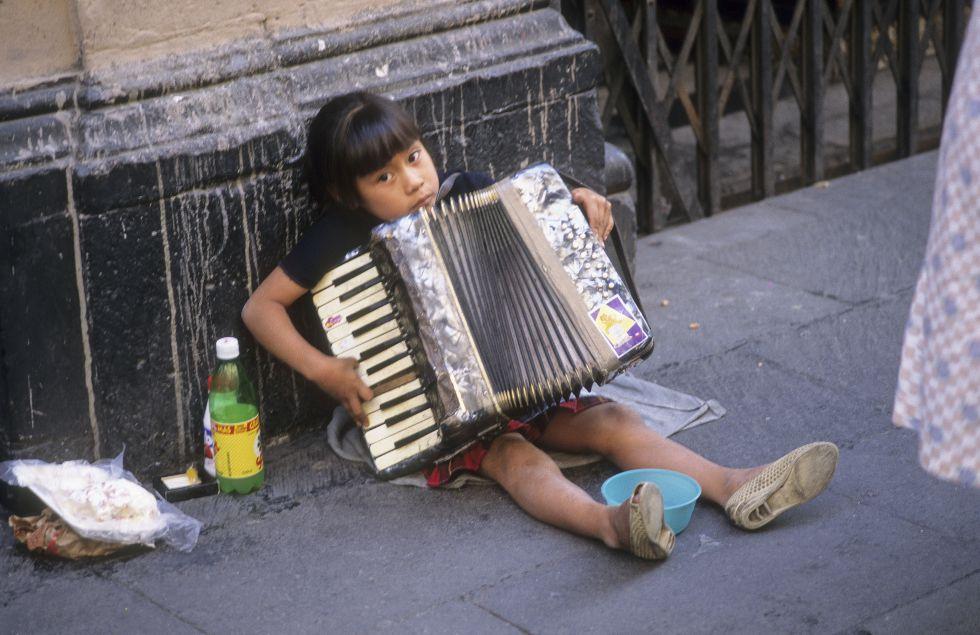 Una niña toca el acordeón en la calle, en Ciudad de México.