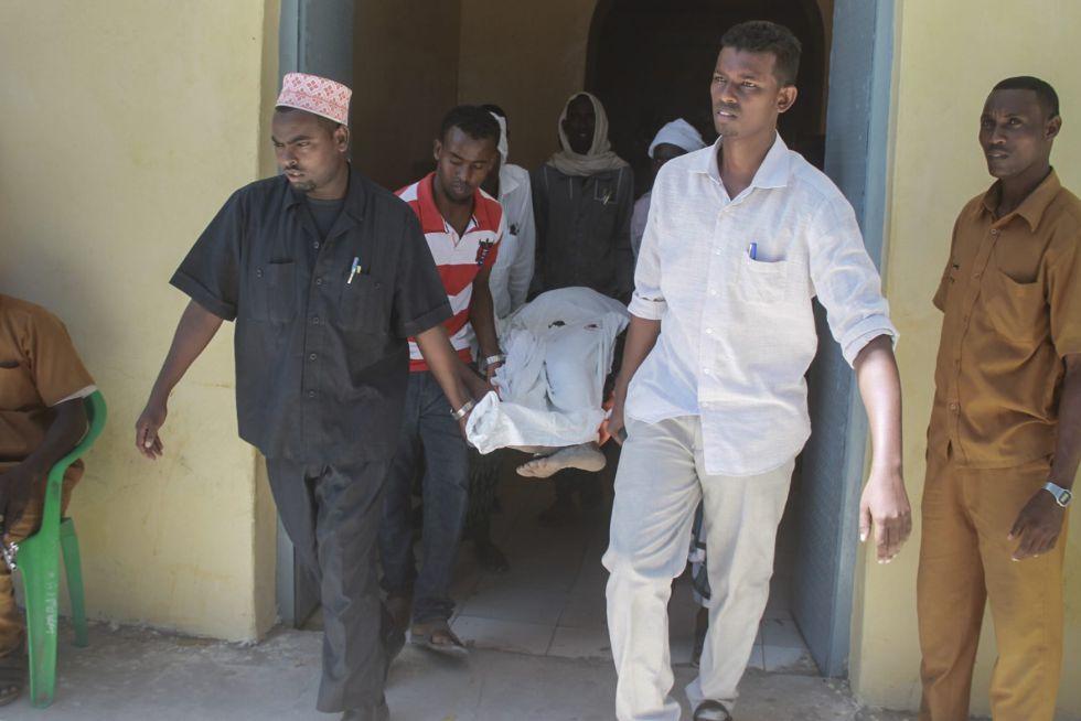 Un grupo de hombres traslada a la víctima de un atentado de Al Shabab en Mogadiscio este jueves.