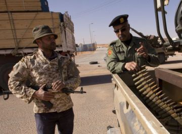 Milicianos Libios revisando el armamento sobre una pick up en el puesto fronterizo de Abu Grein