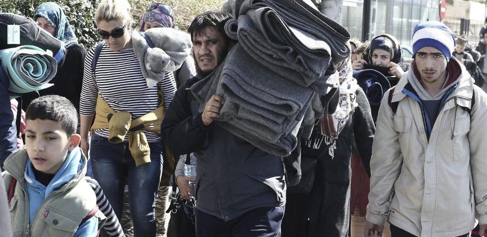 Un grupo de refugiados abandonan el viejo aeropuerto de Atenas, convertido en un campamento temporal.