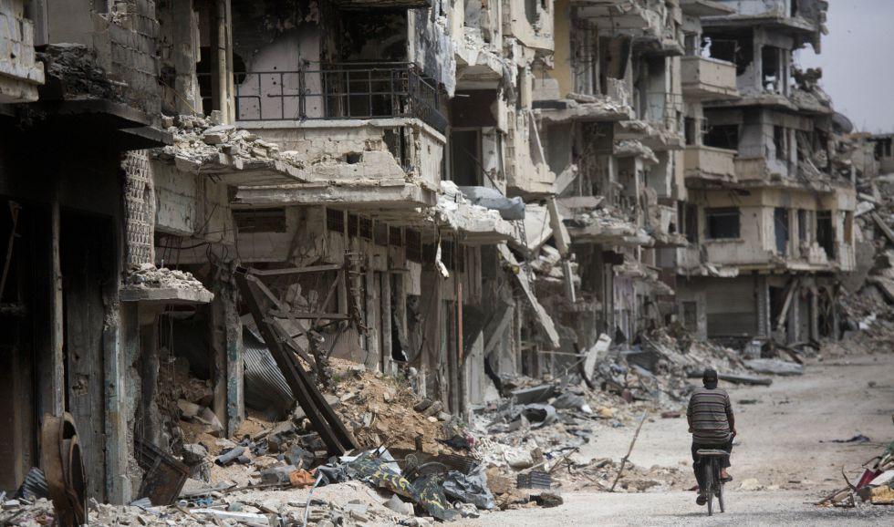 Un hombre monta en bicicleta entre las ruinas de la golpeada Homs.