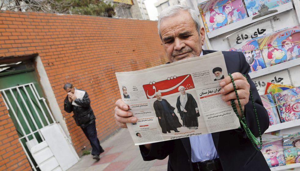 Un hombre sostiene un periódico, este domingo en Teherán, con las imágenes de Rafsanjani y Rohaní.