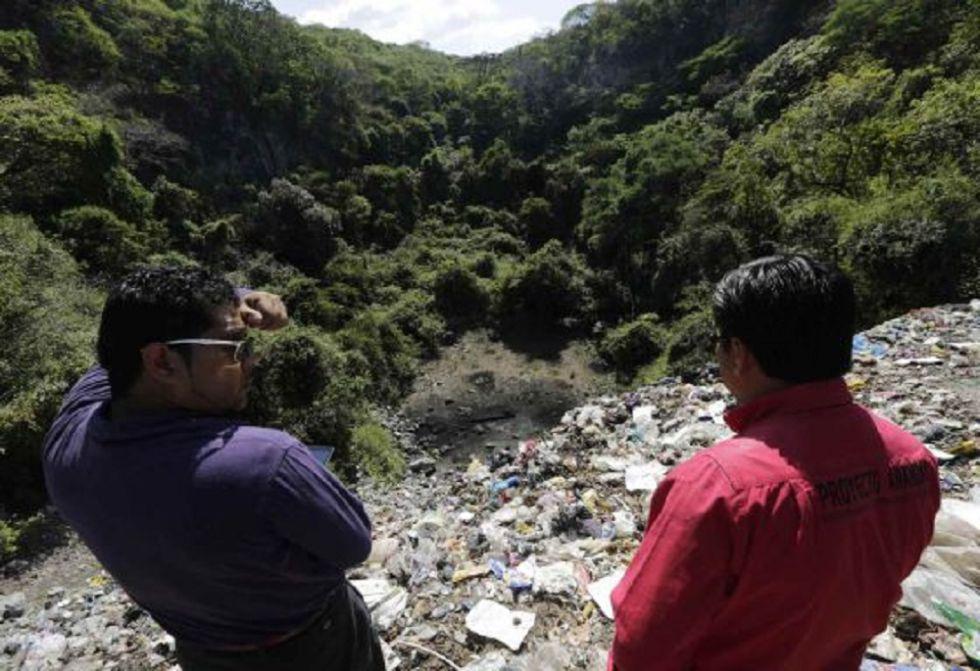 Dos personas observan el basurero de Cocula, Guerrero.