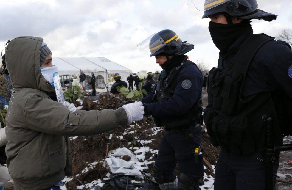 Un niño ofrece flores a la policía este lunes en una manifestación contra el desmantelamiento de la Jungla de Calais.