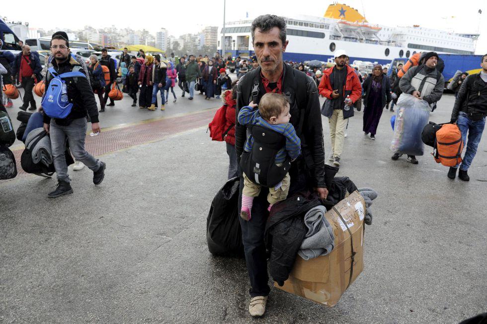 Un migrante llega este martes con un bebé a Atenas desde las islas.