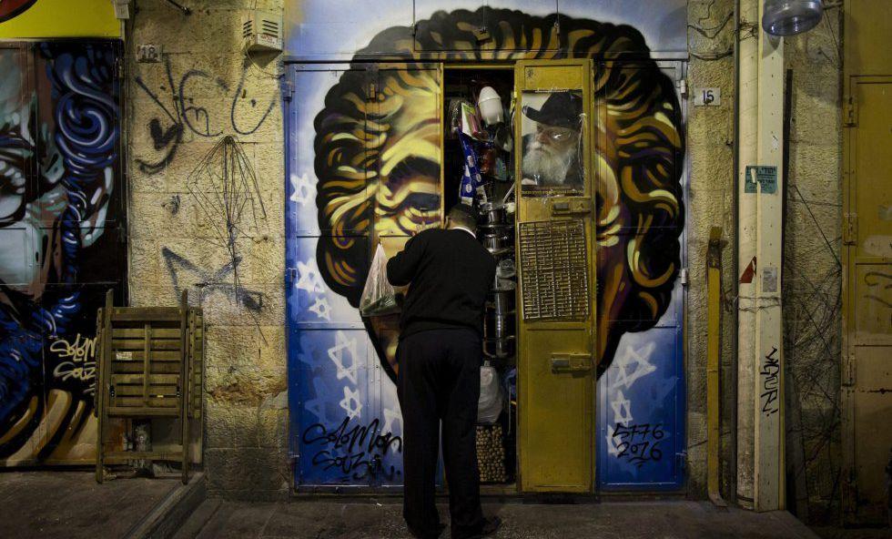 Un comerciante cierra las puertas de su establecimiento en el mercado Mahane Yehuda, decorado con un grafiti del artista callejero Solomon Souza, en Jerusalén.