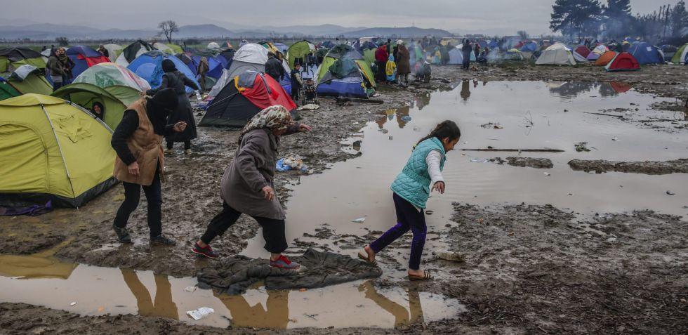 Refugiados caminan por el barro en un campamento cercano a Idomeni, en la frontera entre Grecia y Macedonia.