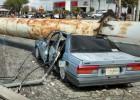 El viento derriba un anuncio sobre dos autos en México