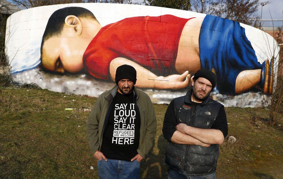 Los artistas Justus Becker, a la derecha, y Oguz Sen este jueves frente al grafiti de Aylan en Fráncfort.