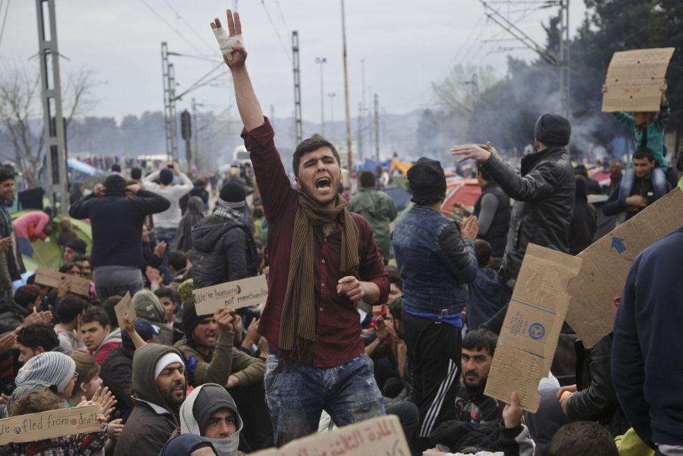 Refugiados e inmigrantes atrapados en Idomeni, en el linde entre Grecia y Macedonia, reclaman este sábado la apertura de la frontera.