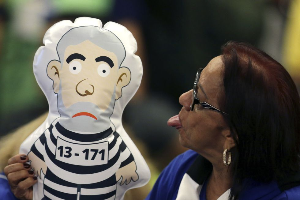 Una mujer con un muñeco de un Lula preso