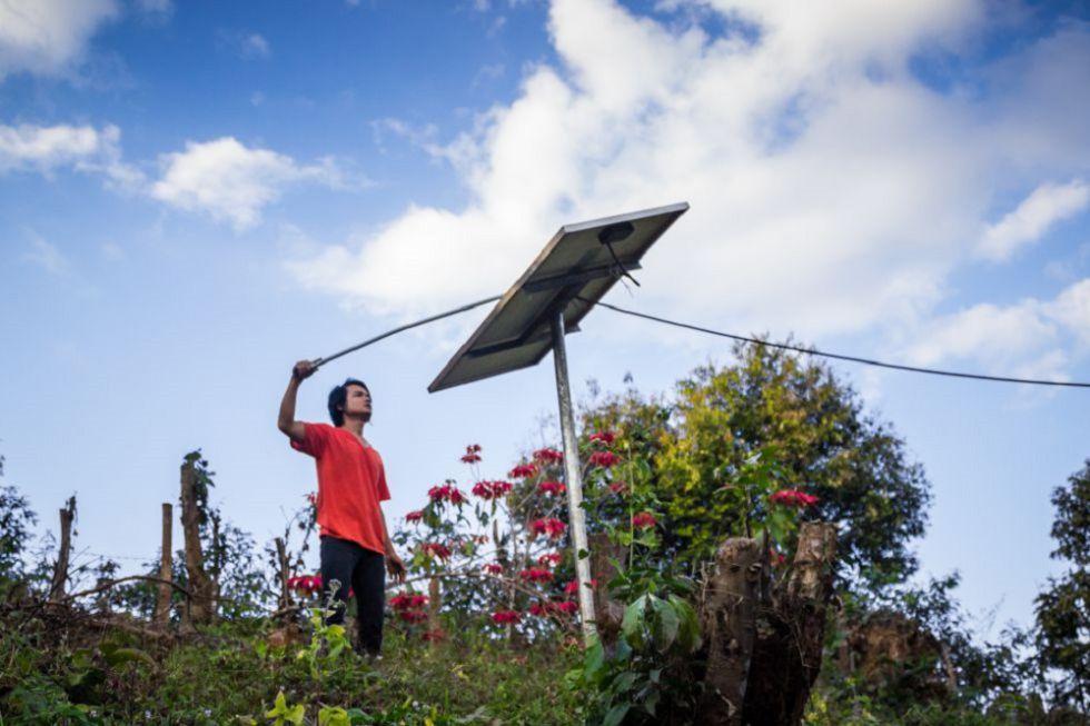 Un joven junto a un panel solar en una aldea de Tailandia.
