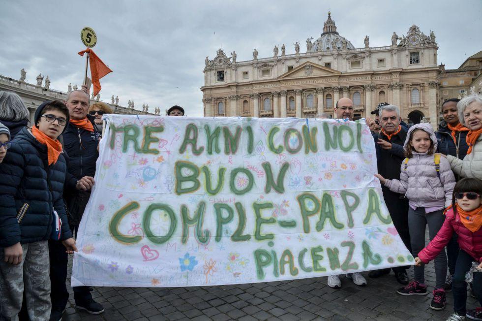 Varios fieles sostienen una pancarta con la que felicitan su tercer aniversario de papado a Francisco.