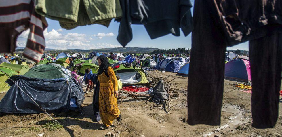 Una mujer camina junto a ropa tendida en el campamento de refugiados de Idomeni, en la frontera entre Grecia y Macedonia.