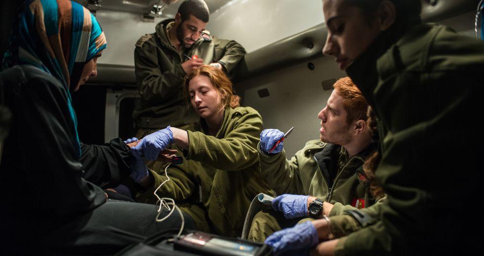 Militares paramédicos israelíes atienden a un grupo de sirios en los Altos del Golán.