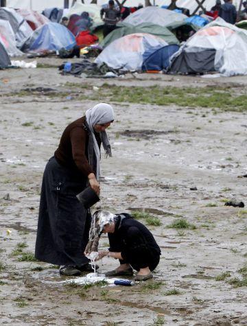 Una mujer ayuda a otra a lavarse el pelo en el campo de refugiados de Idomeni.