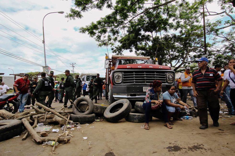 Familiares y amigos de los 28 mineros desaparecidos bloquean una carretera en Tumereno para reclamar respuestas.