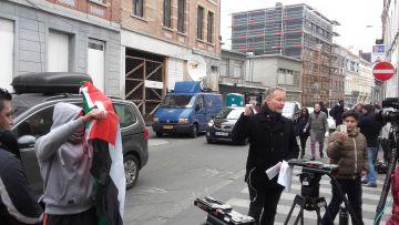 Momento en que un hombre saca una bandera palestina durante una retransmisión televisiva frente a la casa de Abdeslam.