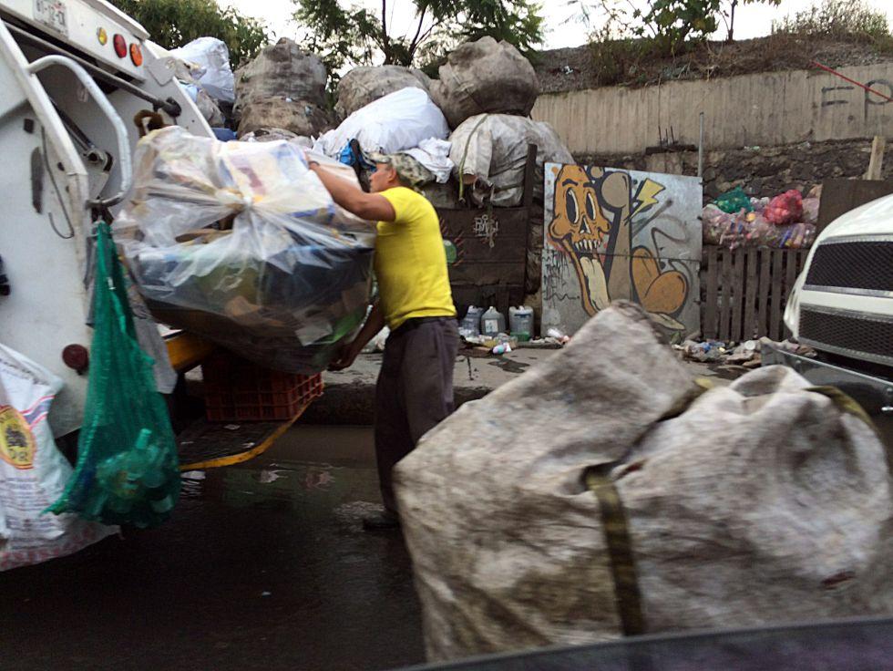 Un recolector separa la basura en el camión, en la Ciudad de México.