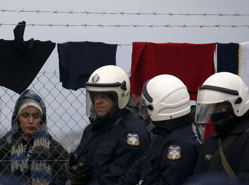 Una muijer mira a policías griegos en la frontera con Macedonia.