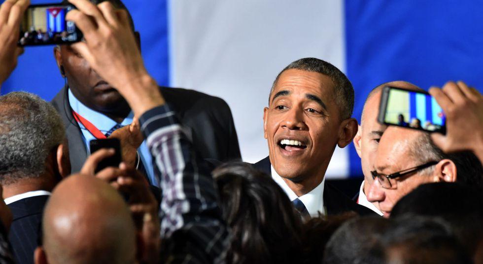 Obama saluda a la prensa.