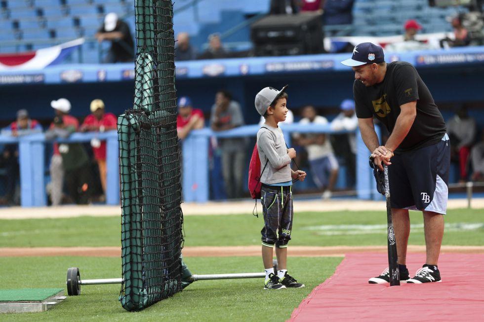 Un jugador de los Tampa Bay Rays habla con un niño cubano en el Estadio Latinoamericano