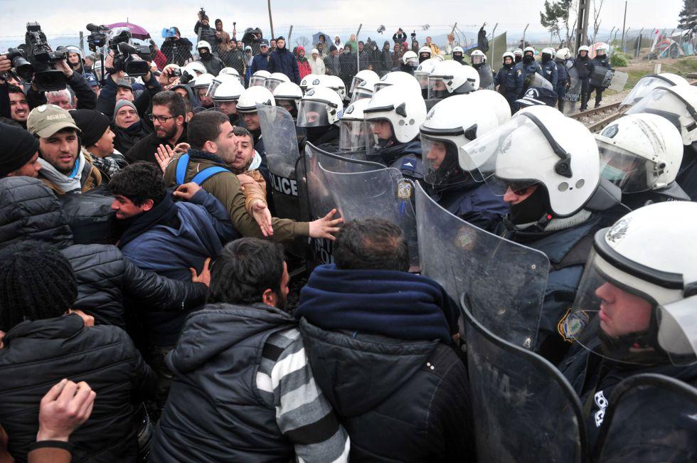 Migrantes ante una barrera policial, este domingo en Idomeni.